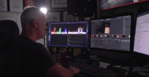 Image of man sitting at computer screen doing video editing