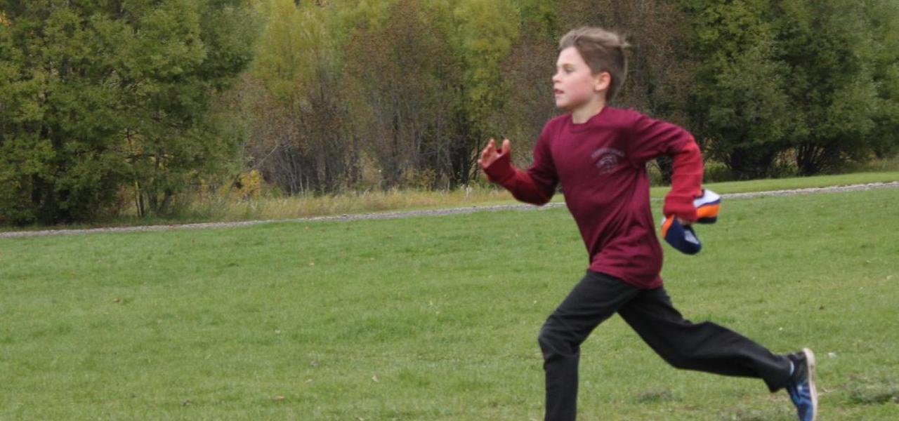 Student running with autumn trees in background.