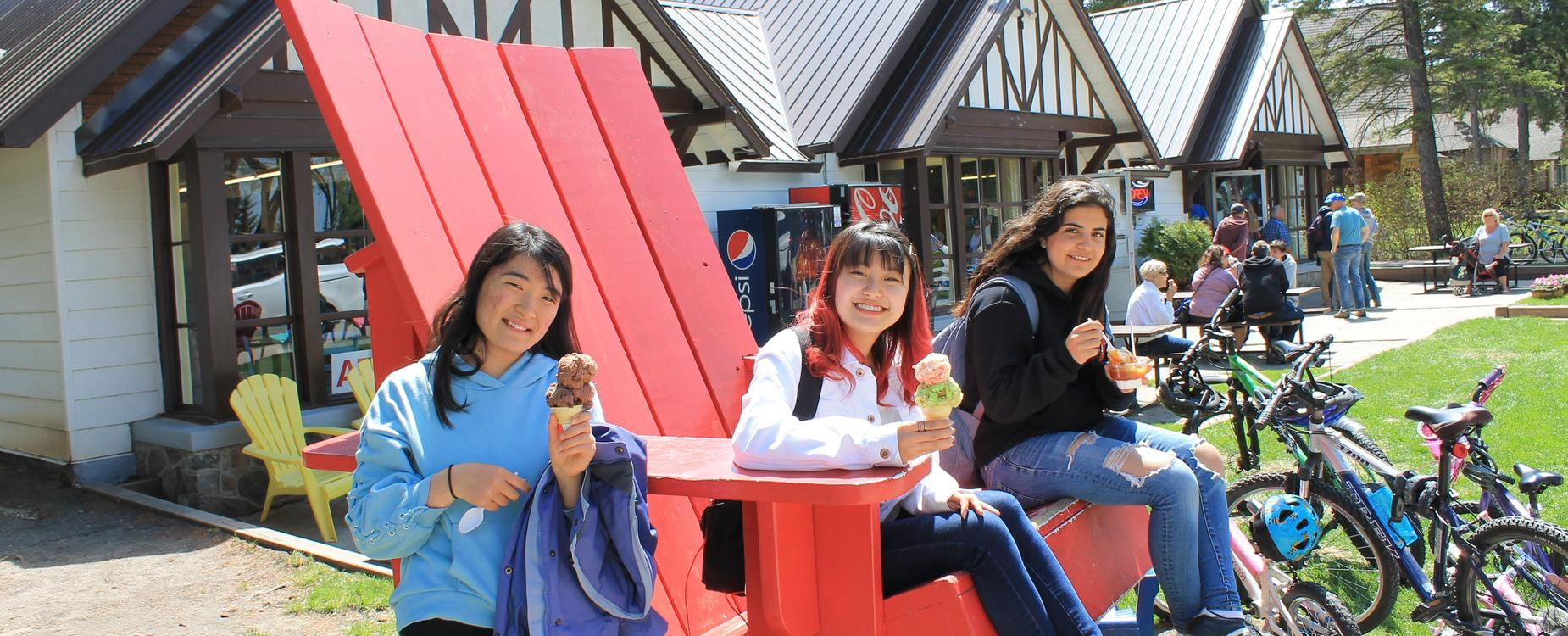girls sitting on a large red bench