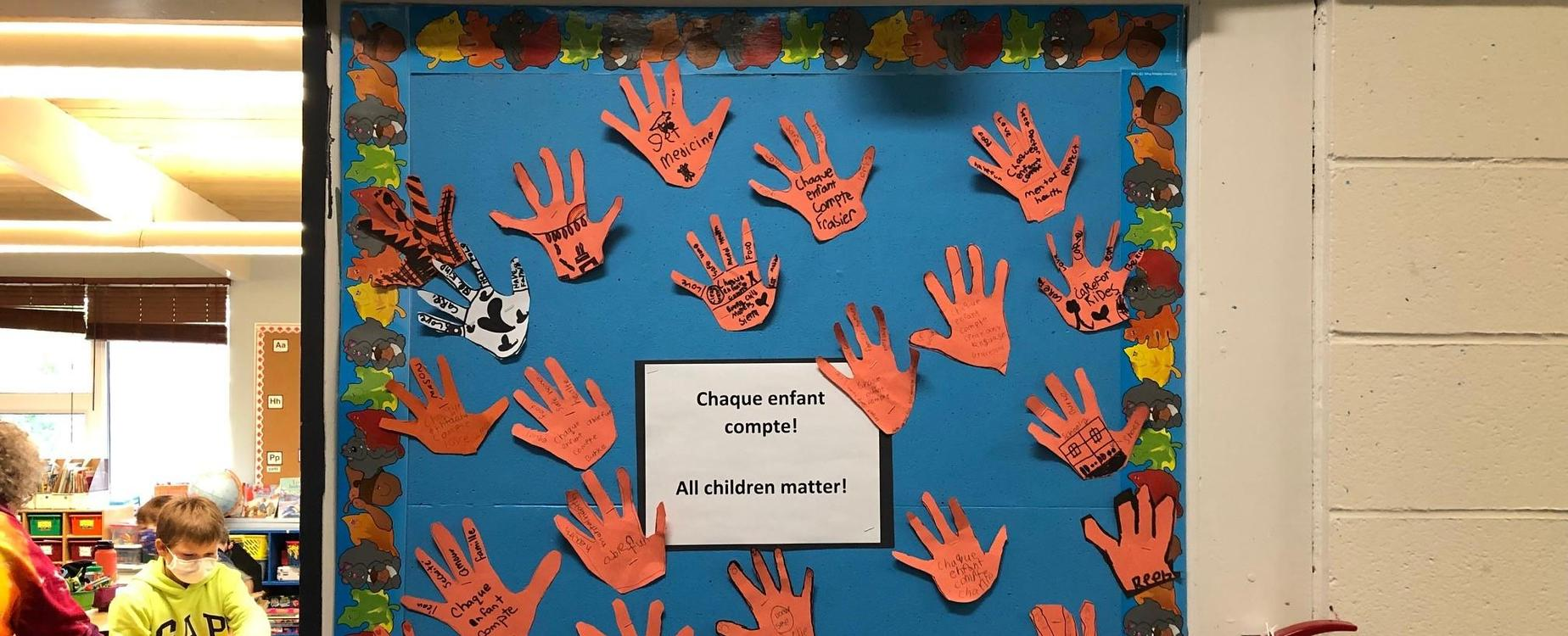 A classroom billboard decorated with orange hand prints, and messages recognizing that