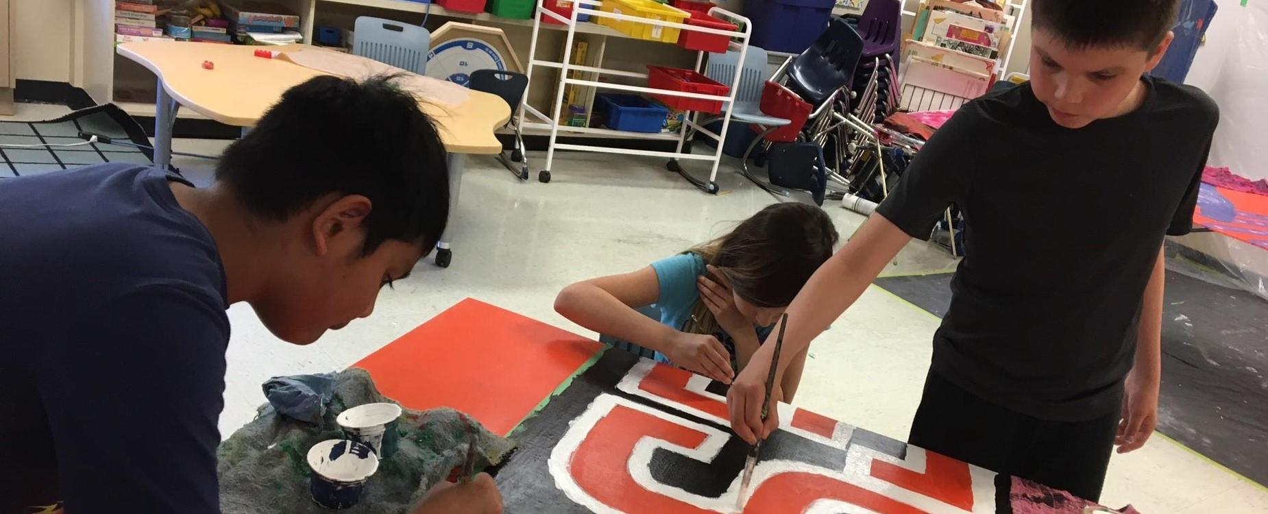 3 students are painting a mural