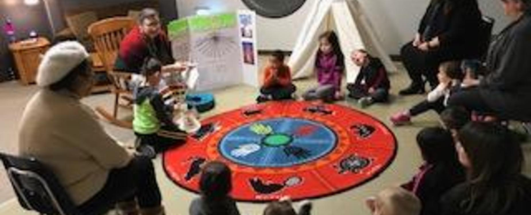 children in a circle around carpet