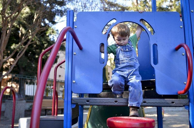 young child climbing on play structure