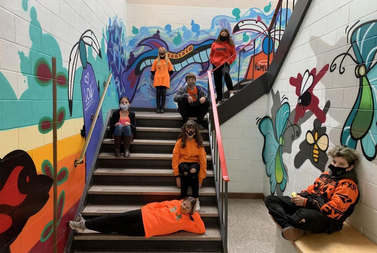 students seated in painted stairwell