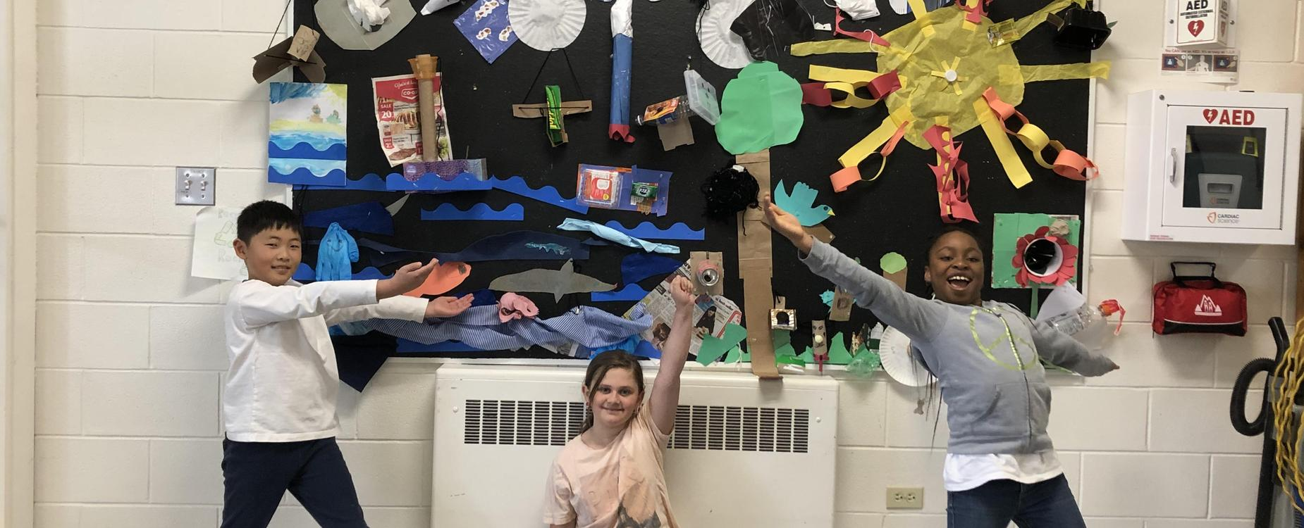 A billboard filled with recycled items turned into art.  It's a landscape with a sun, a sea with flowers and clouds.  3 students are posing in front.