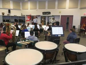 A group of students in a band at Springfield Collegiate in class practicing for the concert. A teacher is at the head of the class.