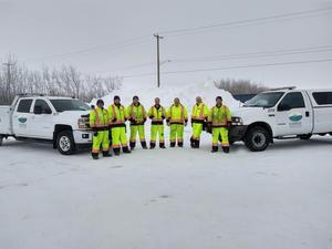 7 Sunrise Mechanic Staff standing in between two half tonne trucks in winter setting.