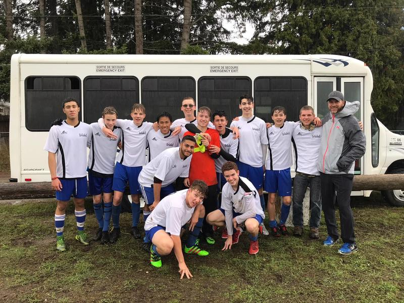 A soggy but happy Sr. Boys Soccer soccer team poses in front of the school bus.