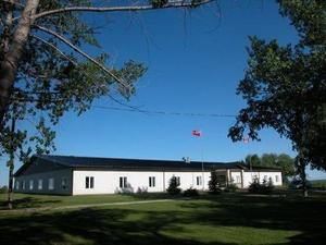 A picture of Springwell School. The building is white and roof is black.    Trees are situated around the school grounds.
