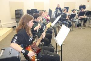Students sitting in a row playing their instruments at a concert.